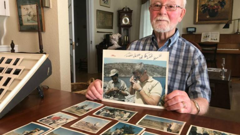 a man holding a photograph up to the camera