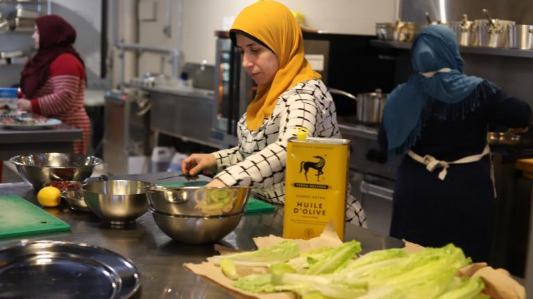 women working in a kitchen from the article Newcomers cook up tastes of home at Thunder Bay's Culture Kitchen