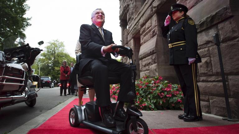 man in a power wheelchair on a red carpet