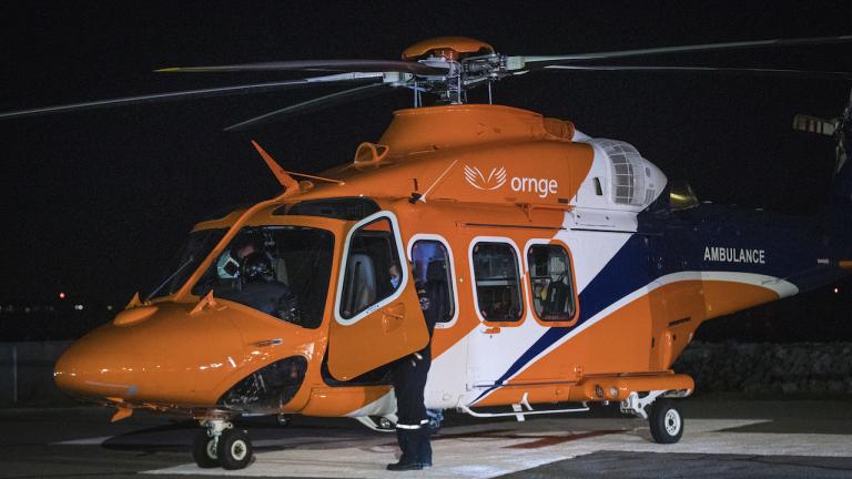 man stands in the open door of a large orange helicopter