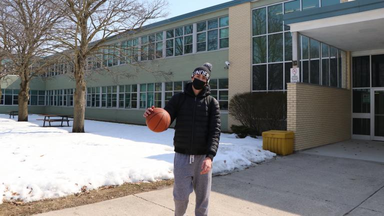 young man in mask, sweat pants, and black coat holding a basketball outside a school