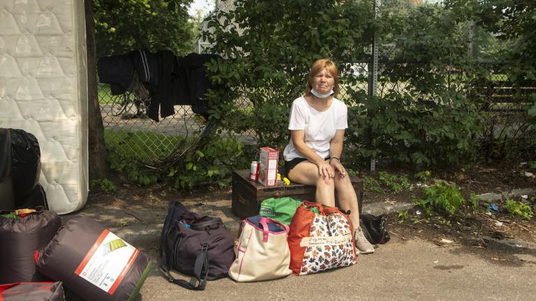 woman sits on a pile of belongings