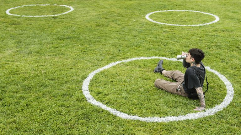 man drinks beer in a chalk circle on grass
