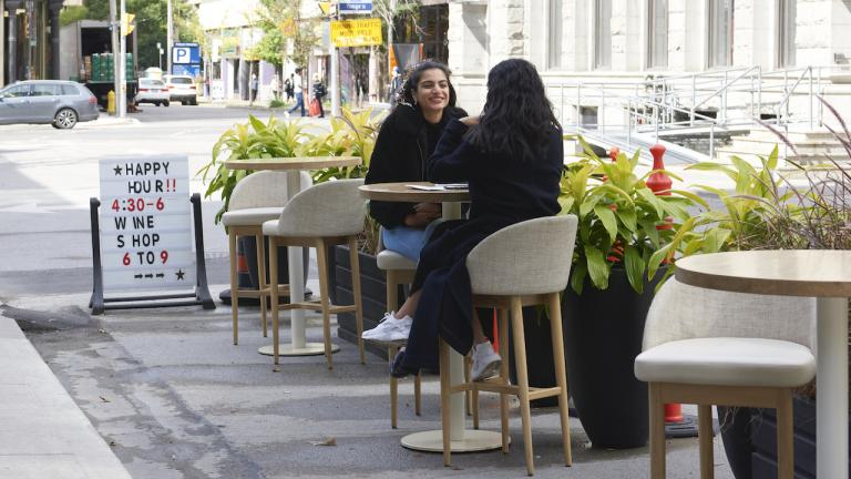 two women sit at a a patio table set up on a street