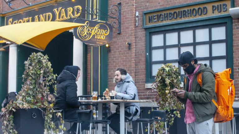 two men sit at a patio table while a masked man checks his phone nearby