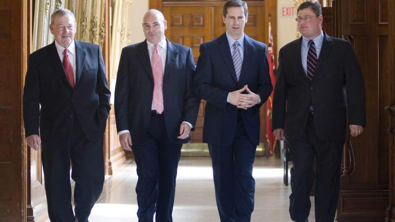 four men in suits walk down a hallway