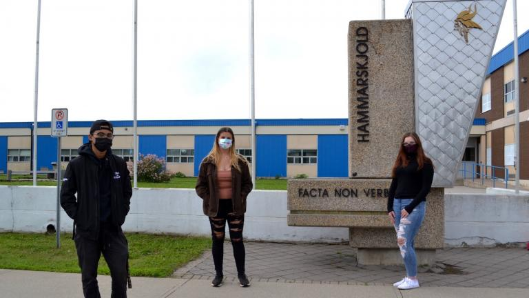 three masked students stand in front of a high school from the article Think you've been working remotely too long? These students haven't been to class since 2019