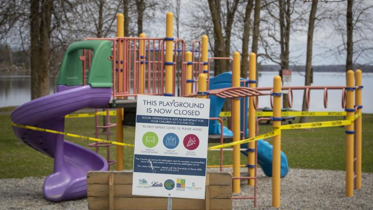 """a playground with caution tape and a sign saying """"playground is closed"""""""