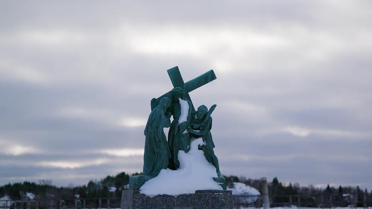 Statue of person holding a large cross.