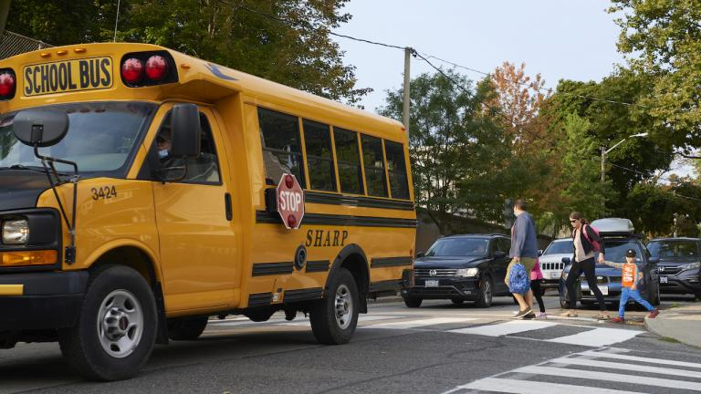 two adults and a child walk past a yellow school bus
