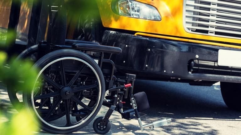 a wheelchair sits next to a yellow schoolbus