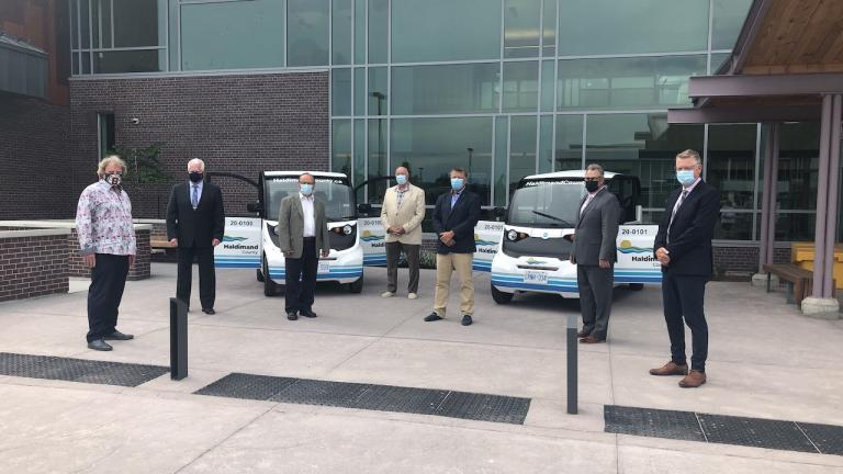 a group of men stand in front of two small vehicles