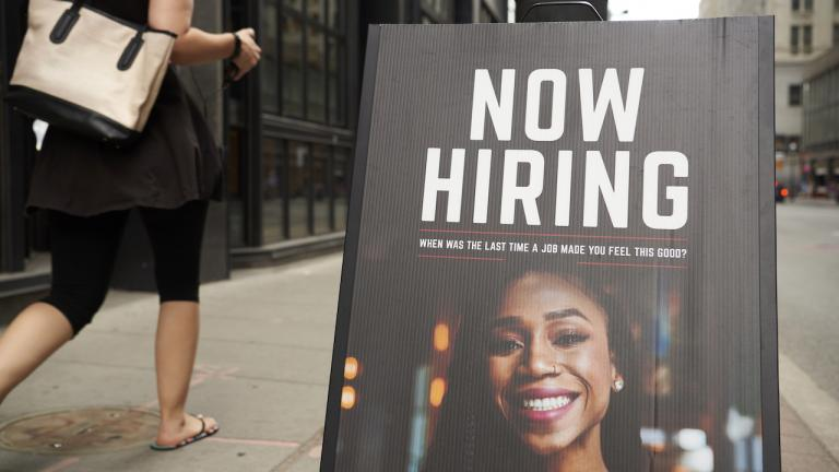 """person walks by sign that reads """"now hiring"""""""