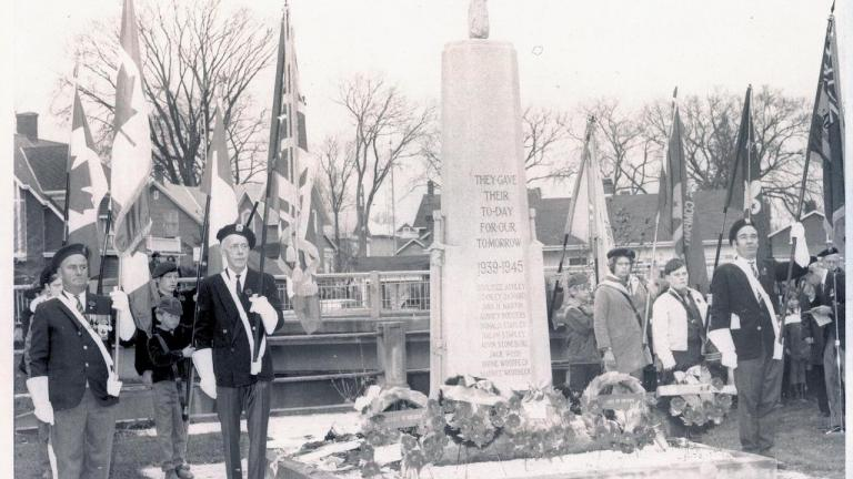 uniformed men stand beside a cenotaph