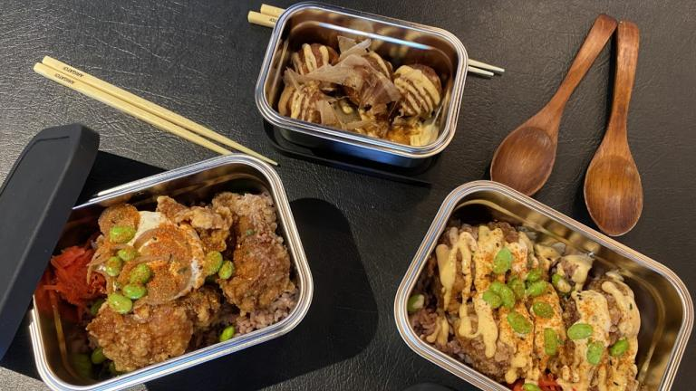 three open containers of food with wooden spoons and chopsticks