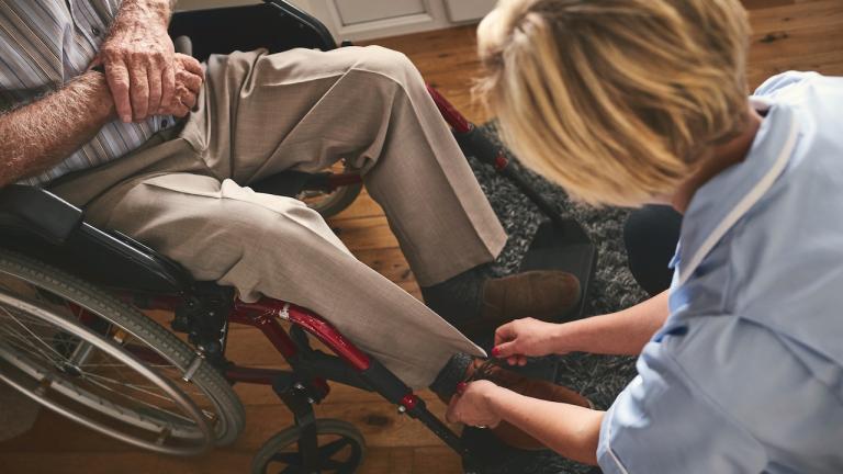 a nurse helping a man using a wheelchair