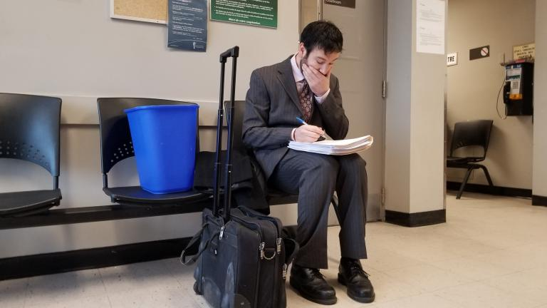 Man in a waiting room filling out forms with his hand over his face, there is a blue bin and a wheeled case beside him