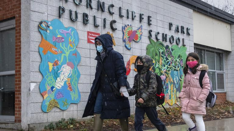 a masked family walks past a school