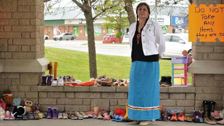 a woman with long hair and a blue skirt stands in front of rows of shoes from the article 'Not forgotten children': Honouring the victims and survivors of residential schools