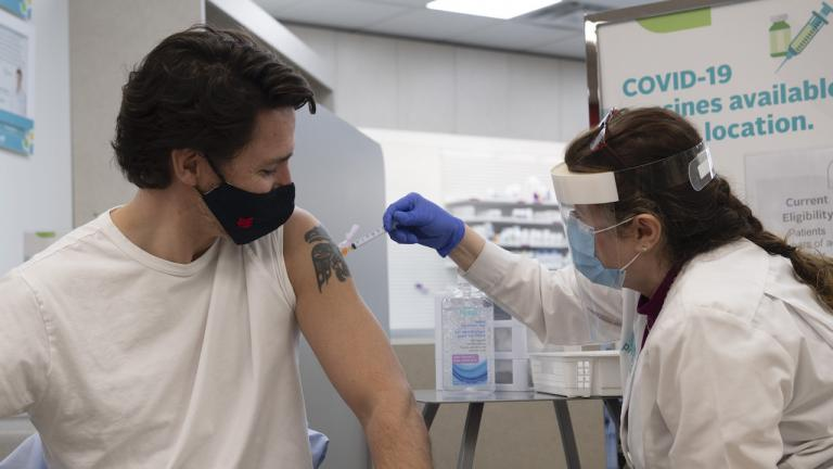a masked man with a shoulder tattoo received a shot from a women in a face shield from the article Dear Justin Trudeau: Pay people to take the vaccine