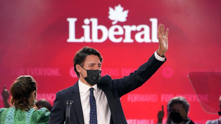 "a man masked man waves under a sign reading ""Liberal"""