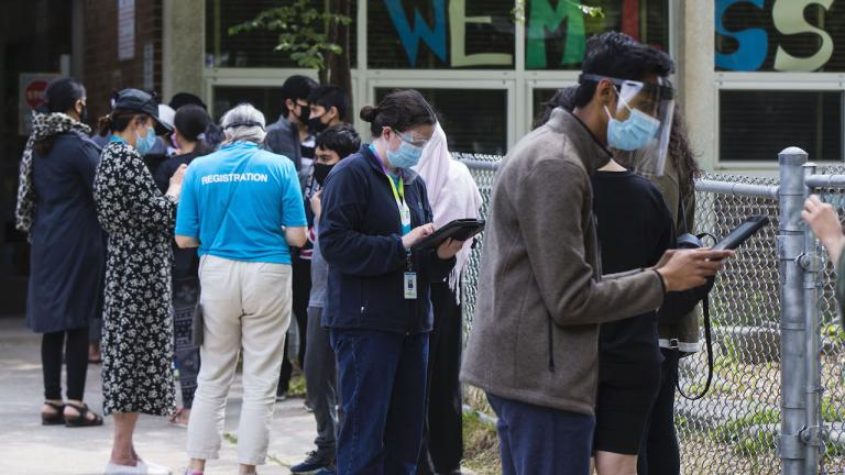 masked people stand in line