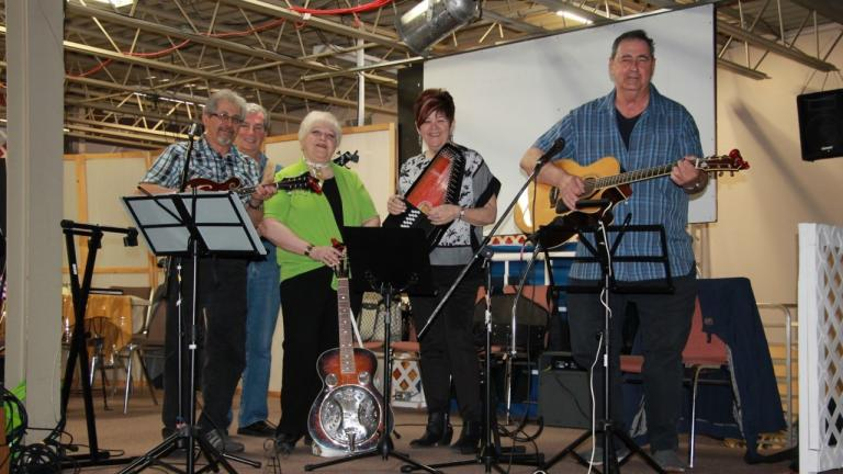 two women and three men hold instruments on a stage from the article How seniors are helping seniors during COVID-19