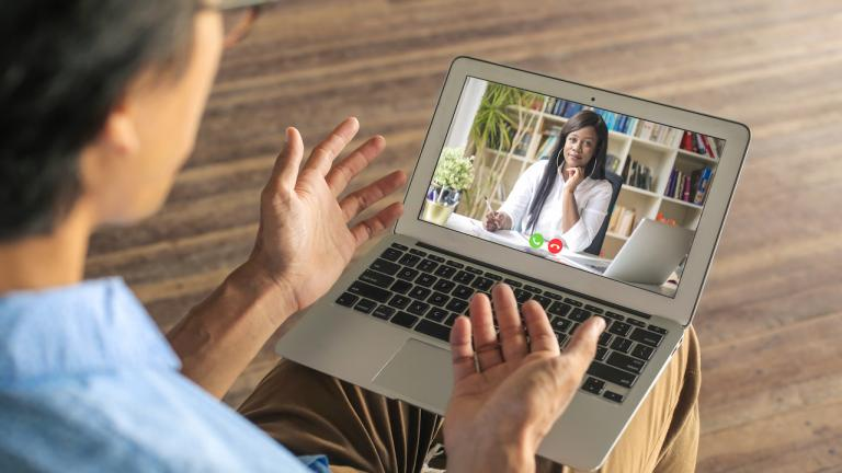 a woman using a lap for a medical video call