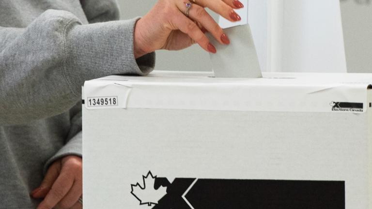 Woman's hand puts ballot in ballot box.