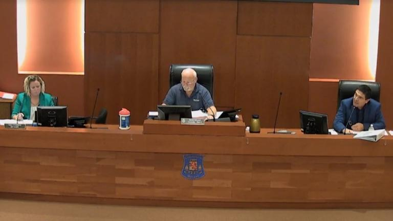 three people behind a desk in a council chamber from the article Should you have to pay to file complaints about politicians?