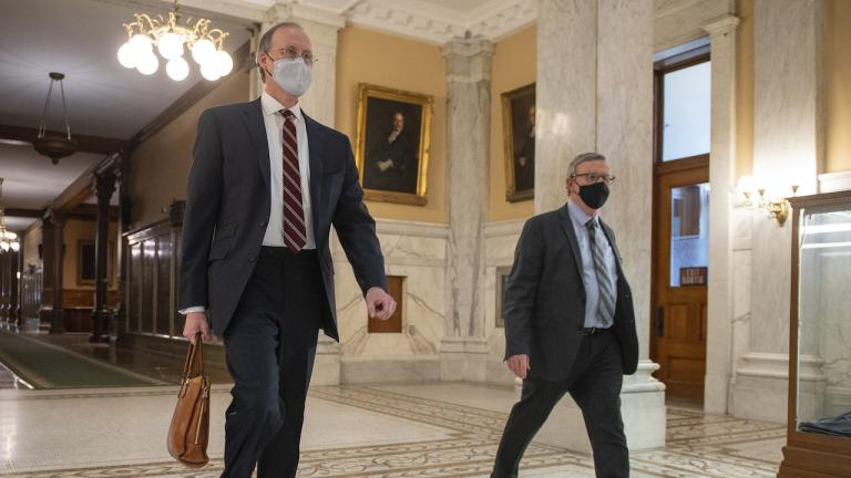 two men wearing suits and masks walk down a corridor
