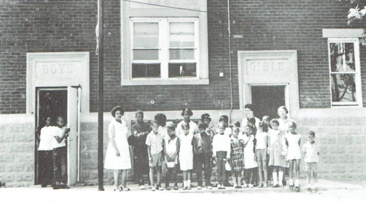 black and white archival photo of children outside their school