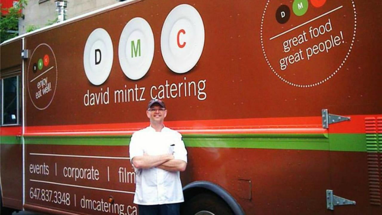 Man stands in front of a food truck.