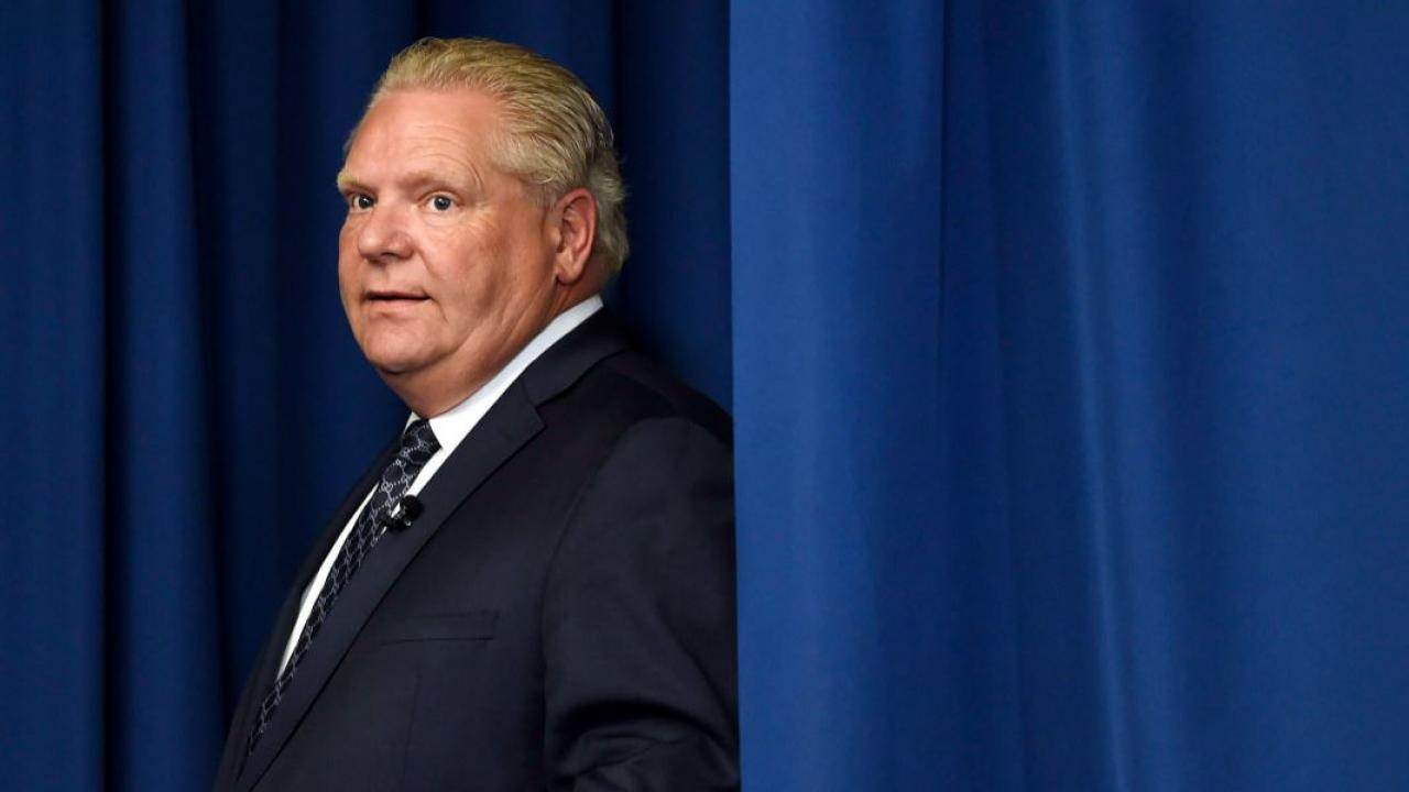 Doug Ford emerging from behind a blue curtain