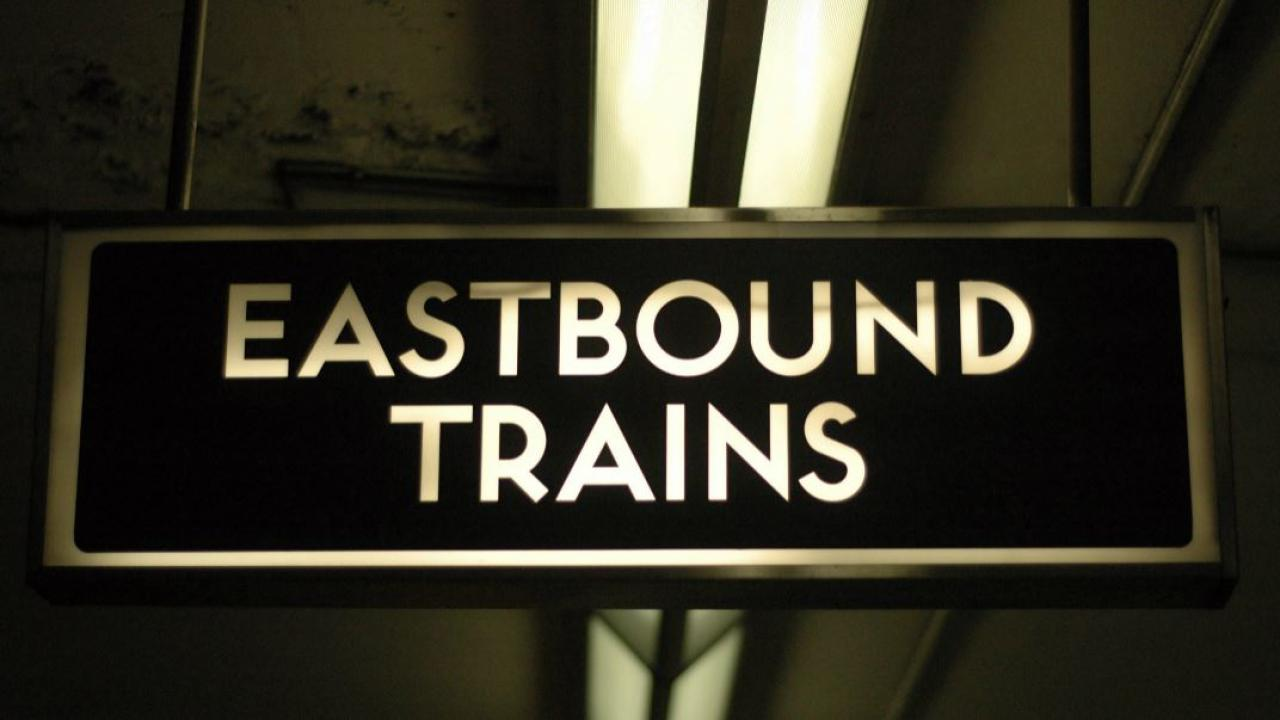 a sign in the subway that says Eastbound Trains