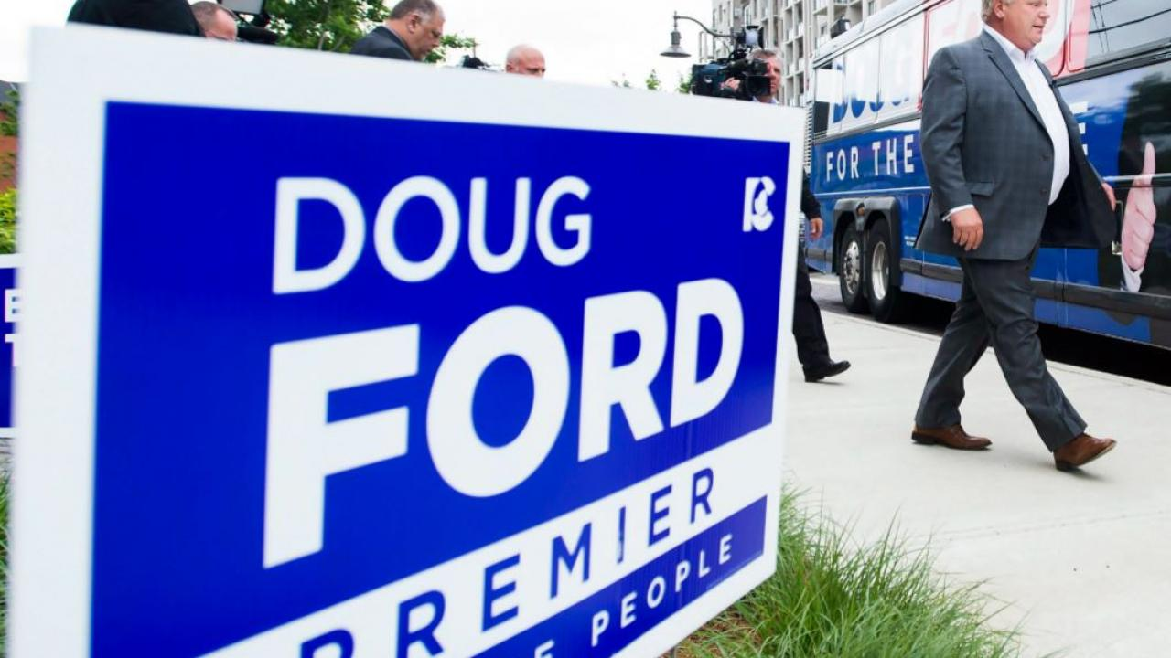 PC leader Doug Ford walking past a campaign sign