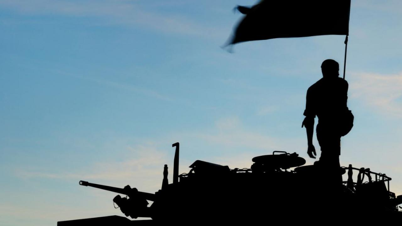 a silhouette of a soldier atop a tank, holding a flag