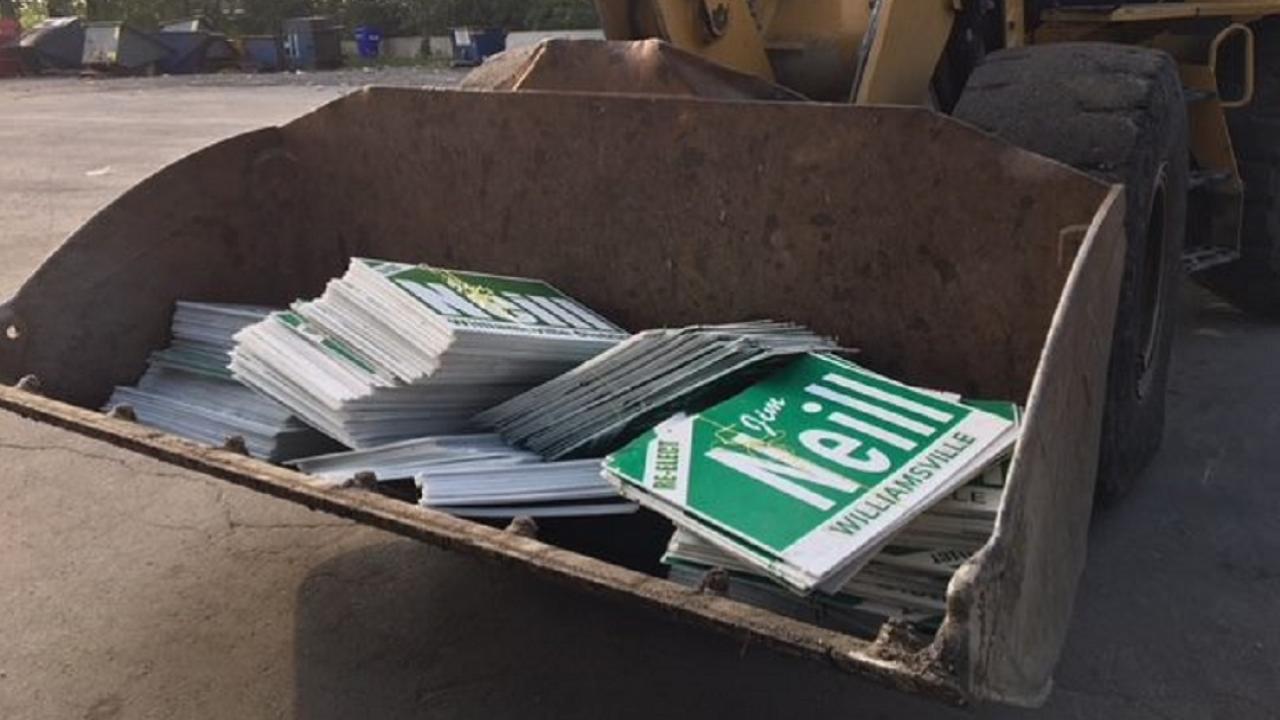 Stacks of campaign signs in a bulldozer scooper