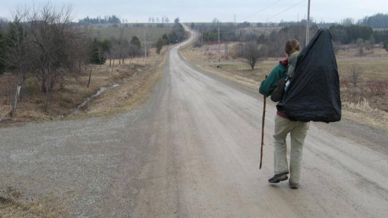 a man walking down a country road with a backpack