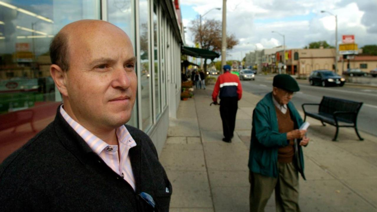 peter milczyn in a pink shirt and black overcoat standing on the street