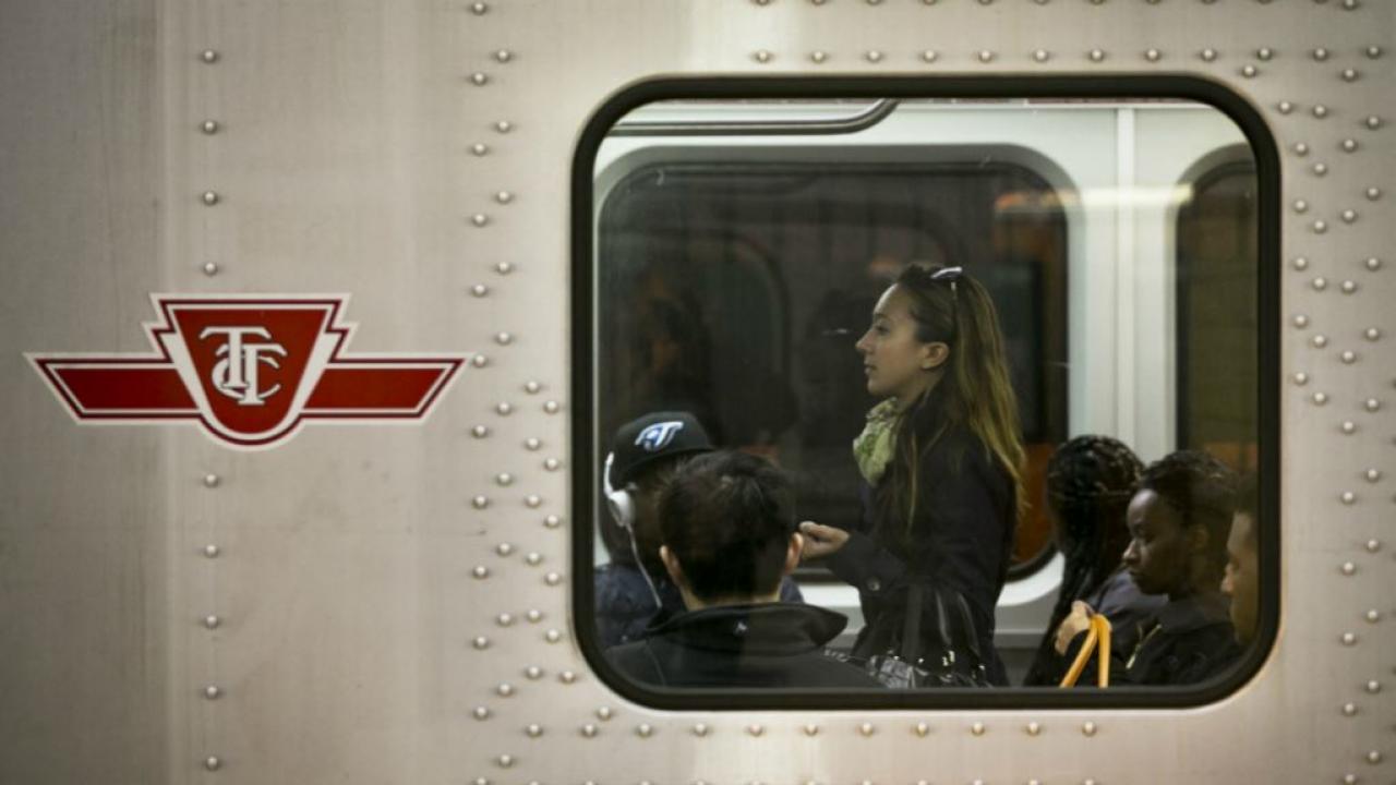 A photograph of a woman seen through the window of a Toronto subway car.