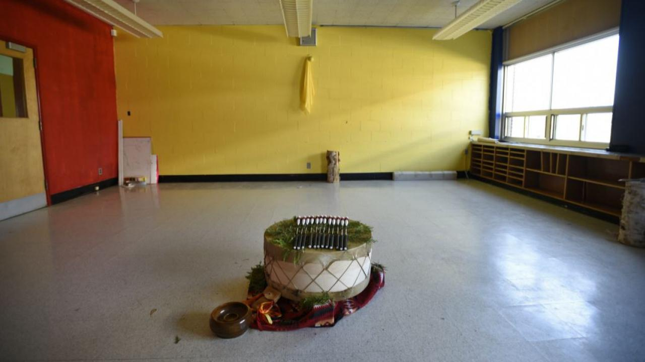 an Indigenous drum set up in a school gymnasium