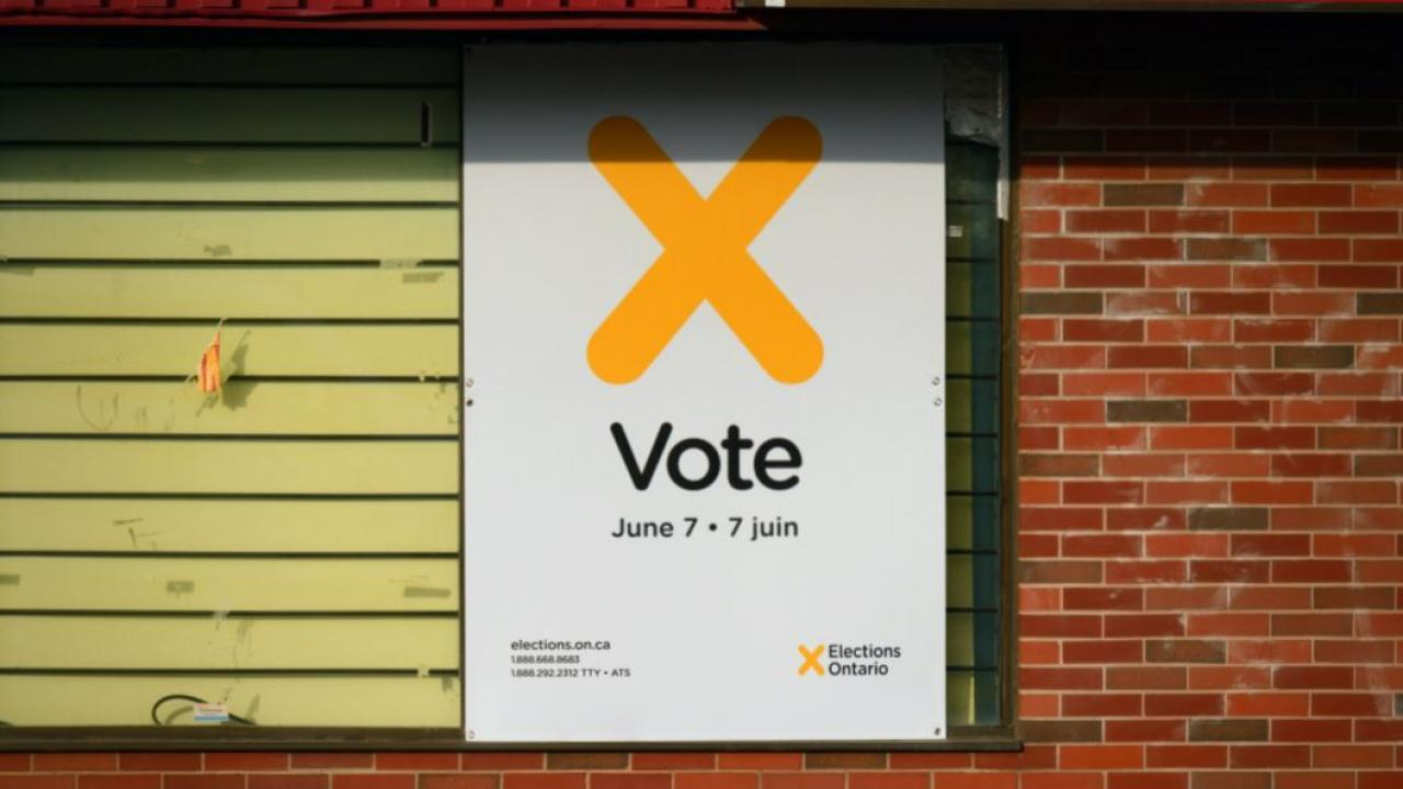 a sign on a wall that says Vote June 7