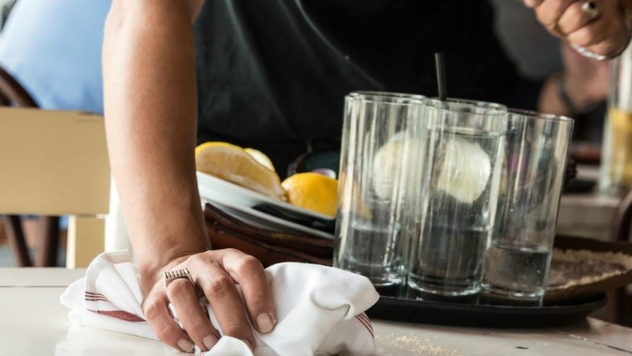 a person cleaning a table in a restaurant