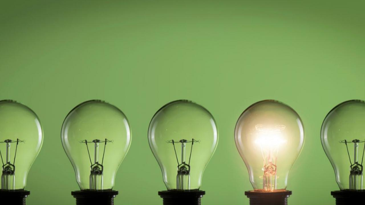 a row of lightbulbs with one lit