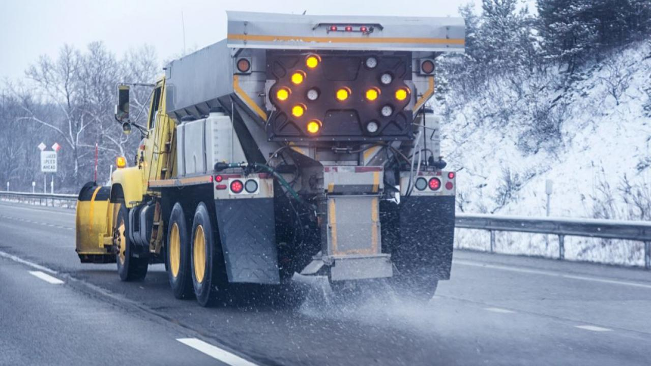 a truck spraying salt on the highway