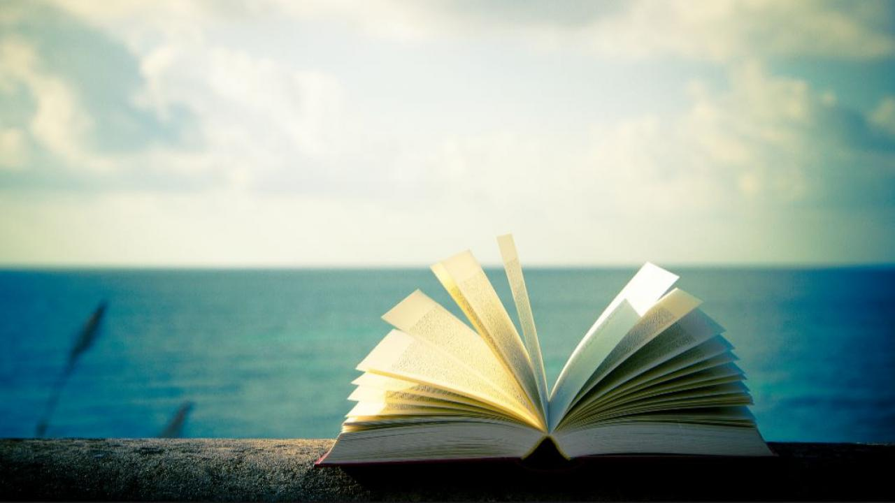 an open book on a beach with a lake in the background