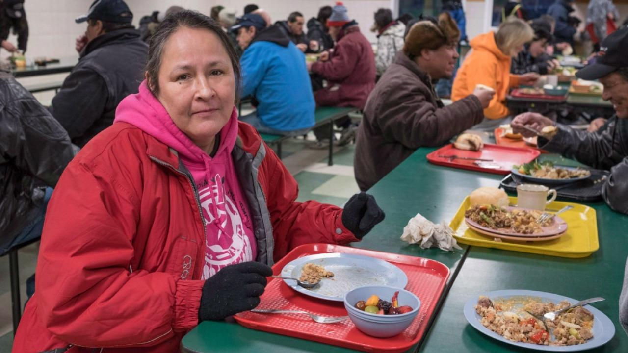 a woman and others eating food in a shelter for homeless people