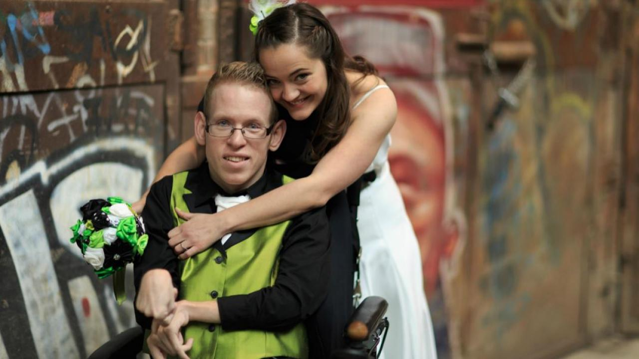 a wedding photo with groom using a wheelchair