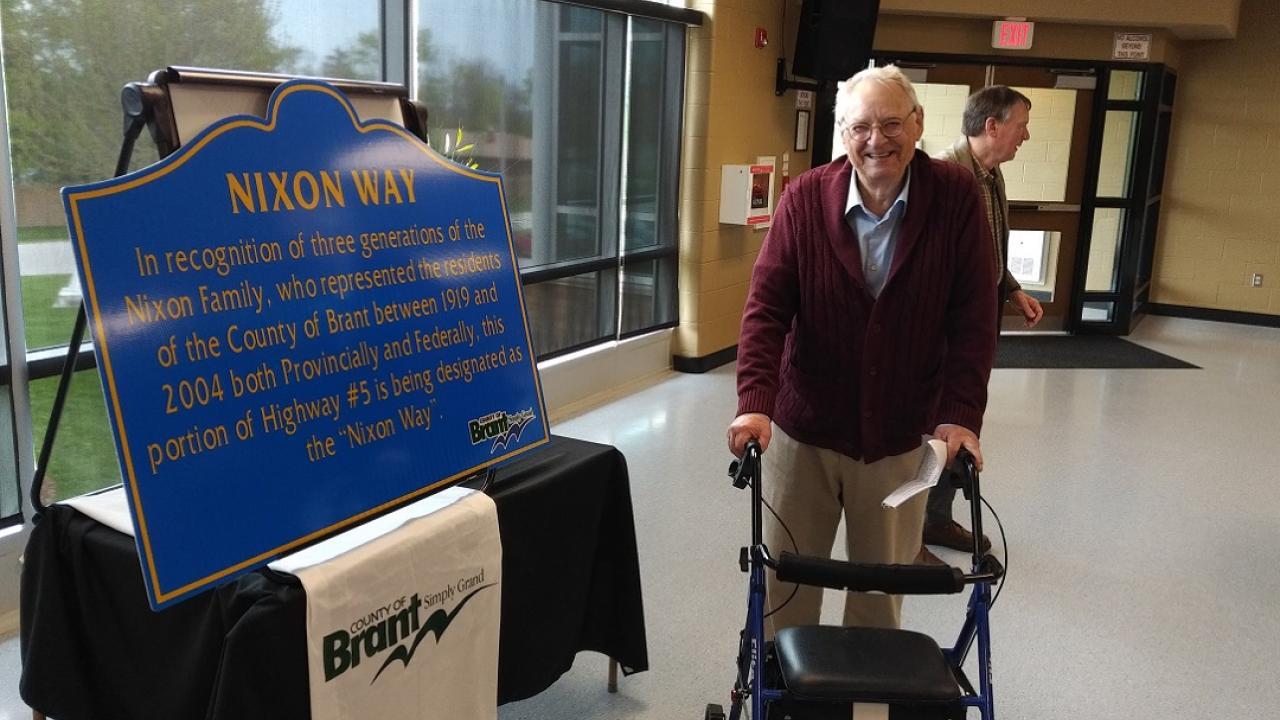 Bob Nixon standing in front of a dedication plaque